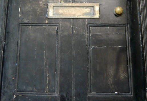 A wooden black door with faded and peeling paint, with rusting knob and mail slot
