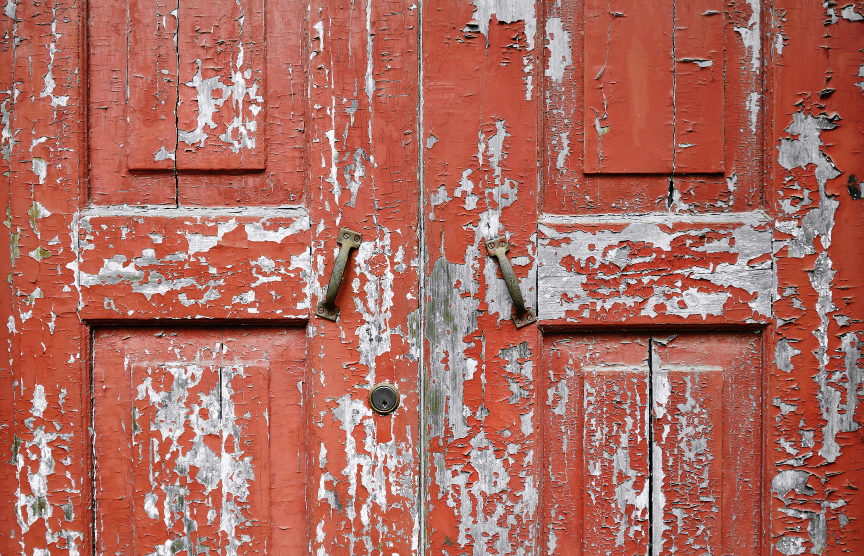 Wooden double door with flaking red paint and cracks
