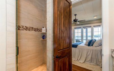 opened wooden door leading from bathroom to master bedroom