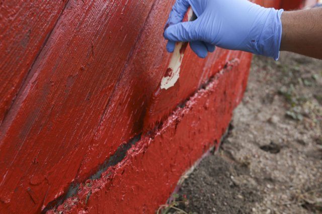 Close-up image of a door being painted by a gloved hand in red paint
